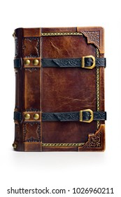 Old leather bound book with the gilded frame, leather straps and brass buckles.The book is captured isolated.