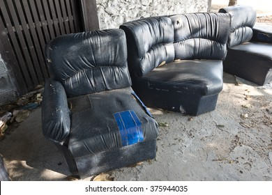 old leather chairs abandoned in old house. Old broken sofa.