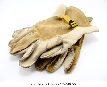 Old leather cowhide work gloves with mesh strap on white background