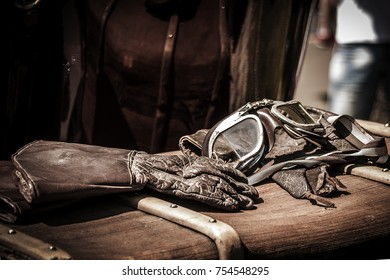 old leather gloves and old glasses on a wooden background