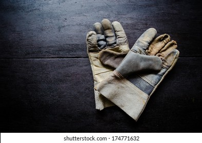 old leather gloves on wooden table