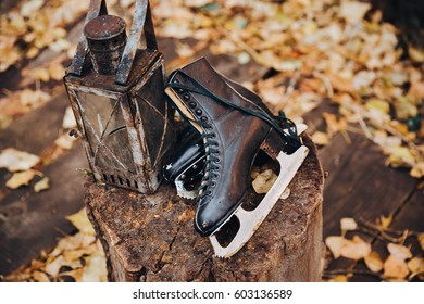 Old leather skates lie on a wooden stump next to a vintage on the background of autumn yellow foliage