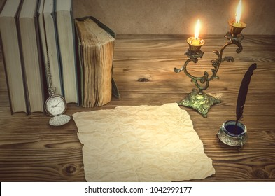 The old letter. Old books feather pen in inkpot, blank paper page sheet and retro pocket watch on retro wooden table background in the light of burning candle. Education. Back to school. Memoirs.
