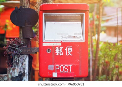 Old letter box with warm light at morning. Red letter box with word post in japan language at countryside.