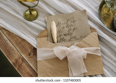 Old letter with vintage handwriting, envelope and feather pen isolated on the table