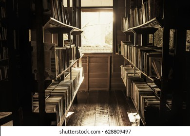 In the old library, the books on the shelves were cluttered, the light shining out of the window in a lonely atmosphere, vintage style.