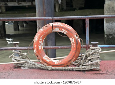 Old lifebuoy or safety torus orange is hanged on the steel fence for dangerous area at river in Thailand.