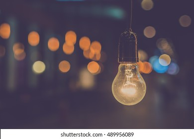 Old light bulb glowing. Vintage filter