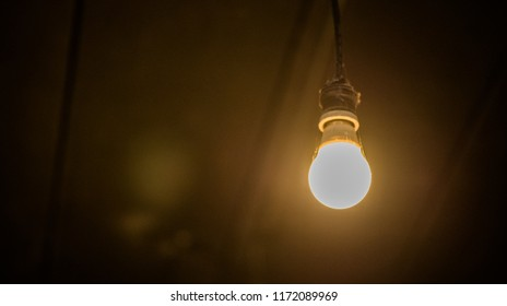 Old light bulb on dark background, decorative in coffee shop. Concept of creativity.