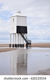 Old light house on the beach with reflection in the water