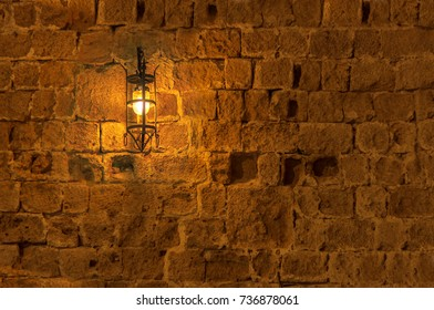 Old light lamp at night hanging on a medieval street fortress wall background