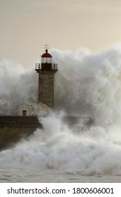 Old lighthouse at the mouth of the Douro River during storm at sea at sunset.