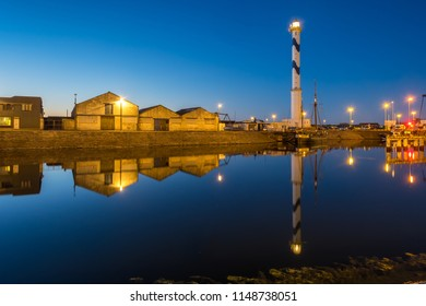 Old lighthouse of Ostend known as 'Lange Nelle' at night, reflected in a commercial dock.
