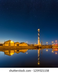 Old lighthouse of Ostend known as 'Lange Nelle' at night, reflected in a commercial dock