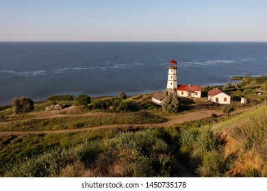 Old lighthouse with a red roof on the sea shore in the morning