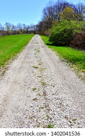 The old limestone aggregate single lane drive though an open field toward a forested area.