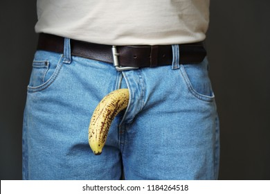 old limp drooping banana hanging from genital area of clothed unrecognizable man, impotence erectile dysfunction or limp-dick concept