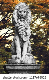 Old Lion Statue with Fall Foliage seen at Cylburn Arboretum in Baltimore, Maryland.