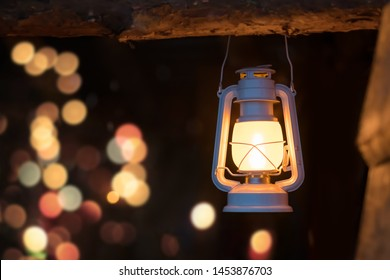 Old lit kerosene lamp hanging from a wooden beam in a shed in a village, northern Norway