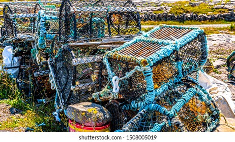 Old lobster / crab cages or fishing traps lying by the garbage on the coast of the island of Inis Oirr, sunny day in Inisheer, an island in the west of the coast of Ireland