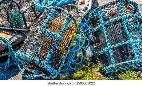 Old lobster / crab cages or fishing traps lying alongside ropes on the coast of the island of Inis Oirr, sunny day in Inisheer, an island in the west of the coast of Ireland