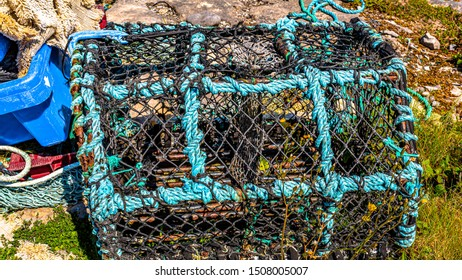 Old lobster/crab basket or fishing traps with plants inside lying next to garbage on the coast on the island of Inis Oirr, sunny day in Inisheer, island in the west of the coast of Ireland