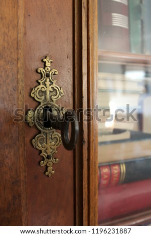 Old Lock And Key On Antique Bookshelf With Glass Doors
