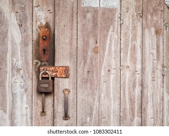 old lock on the wooden door in front of old farmhouse at rustic countryside