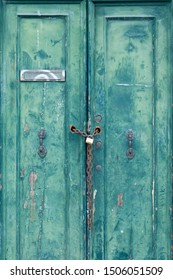 Old locked door with peeling paint, padlock and chain in Venice, Italy