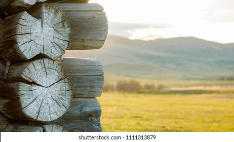old log cabin with a background of the morning village landscape: mountains, field