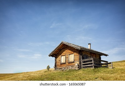 old log cabin at a meadow
