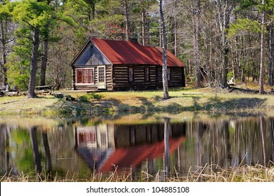 Old Log Cabin reflection in a pond. Michigan forest USA