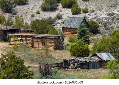 Old log cabins and sheds are part of the El Rancho del las Golondrinas, a living history museum, near Santa Fe, New Mexico.  Wooden ladder leans against cabin.