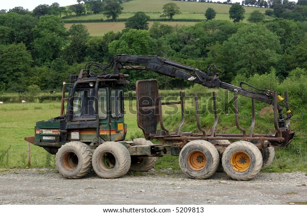 Old log carrying truck standing idle on rough ground with trees and fields to the rear.