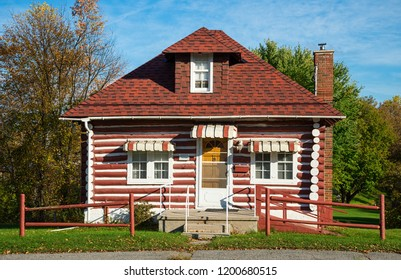 Old log house with red shingle roof