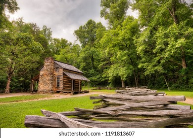 An old log and stone cabin in the green woods with an old wooden fence in the foreground and a grey sky