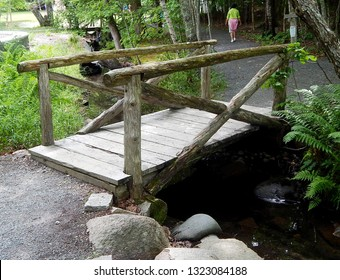 Old log wood bridge over babbling brook on hiking trail in Acadia National Park