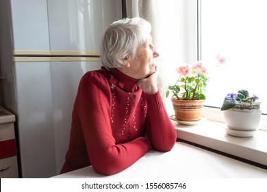 Old lonely woman sitting near the window at home. Concept of quarantine, coronavirus Covid-19. Danger for old people