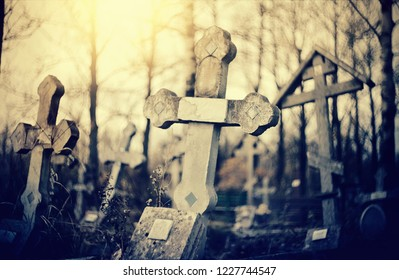 The old lop-sided sepulchral crosses at the cemetery in the evening.