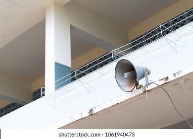 Old loudspeaker on tower in school background.