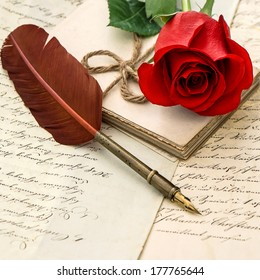 old love letters, red rose and antique feather pen. selective focus