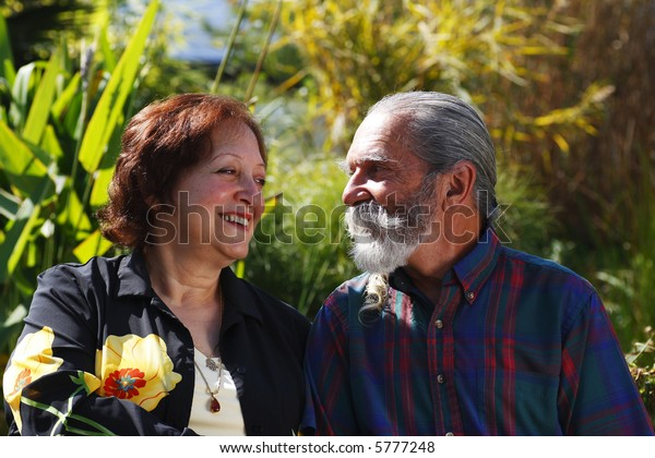 Old Loving couple looking at each other with garden or nature background