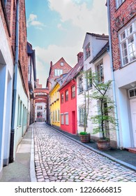 Old Lubeck street with paving stone. Small trees growing in pots. Germany