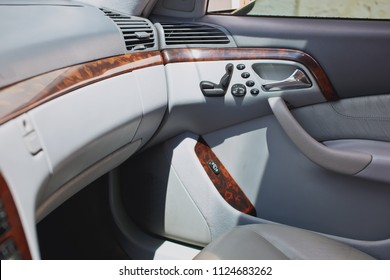 Old luxury modern car interior, beige color, electronic buttons, automatic transmission lever