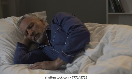 Old male lying in his bed and sleeping, recovery time and healthy sleep, night