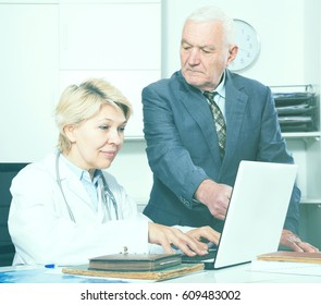 Old male visitor consulting smiling aged woman doctor in hospital