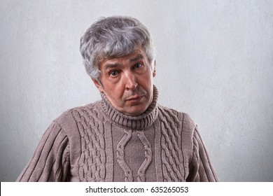 An old male with wrinkles having gray hair dressed in sweater having sympathetic expression isolated over white background. Mature man posing in studio. People and lifestyle conceppt.