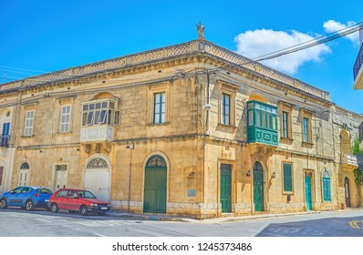 The old Maltese edifice with typical balconies and the sculpture of a Saint on the corner of the roof, Mista town, Malta