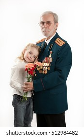 Old man in army uniform with rewards and beautiful little girl on isolated studio background