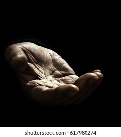 Old man asking for support with outstretched hand with wrinkles on the black background. The concept of infirmity and lack of money and food in the elderly people without sufficient social assistance.